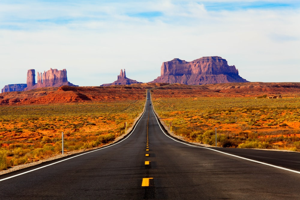 asphalt road in the middle of the desert