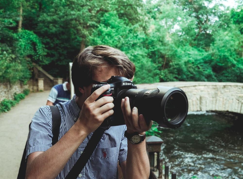 man taking photo using black Nikon DSLR camera