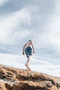 low angle photography of topless man wearing blue shorts standing on rock formation