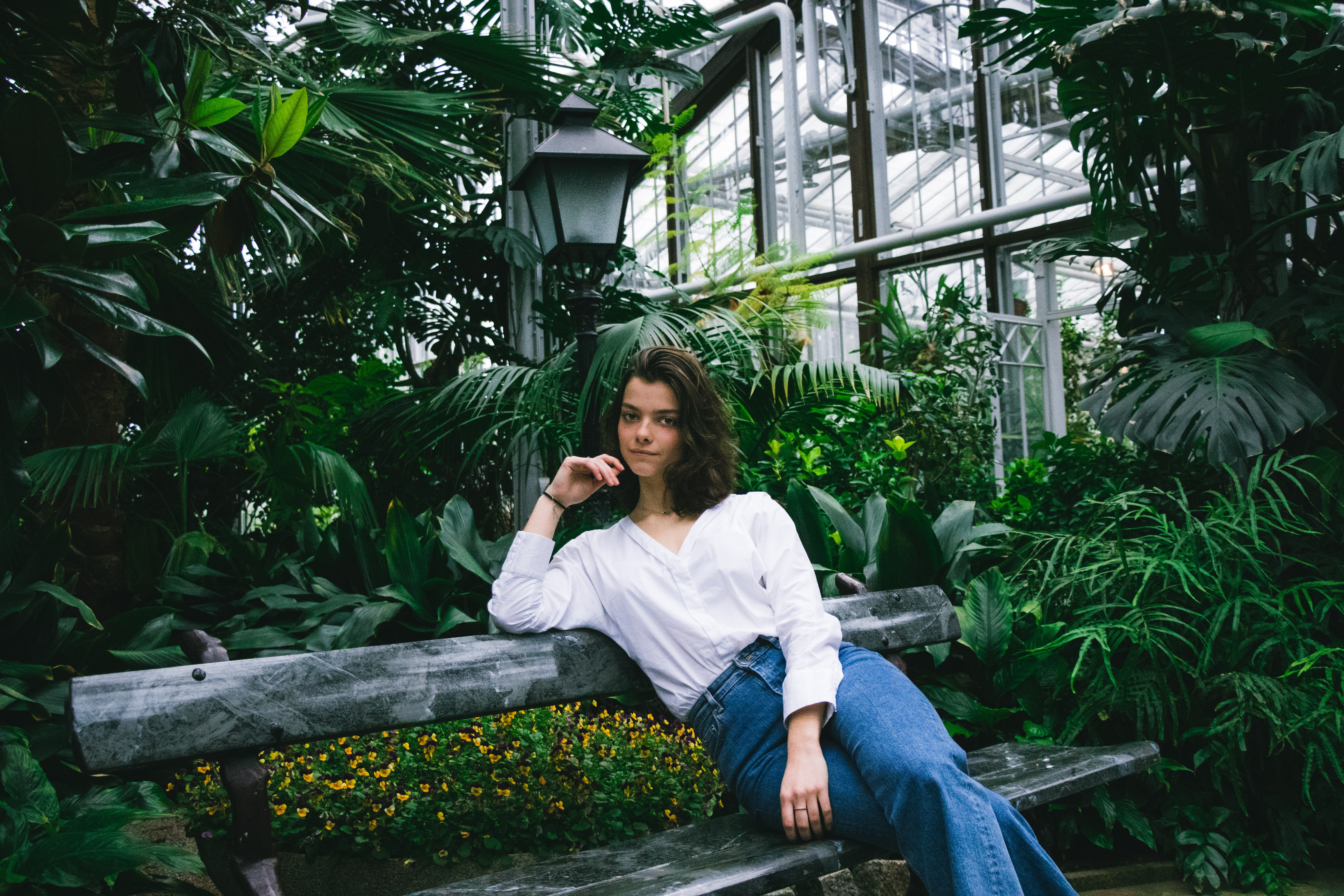 woman sitting on gray wooden bench surrounded with plants
