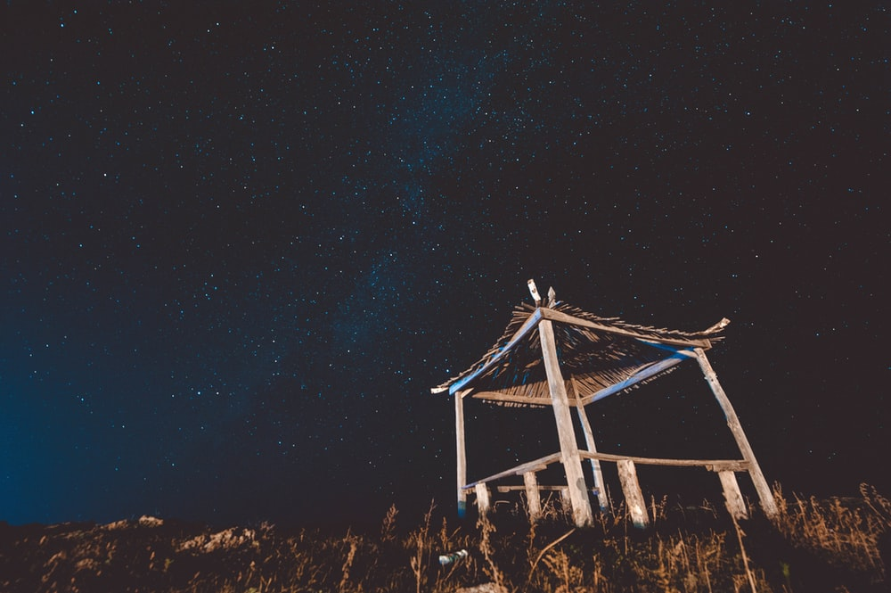 bottom view of wooden hut and starry sky