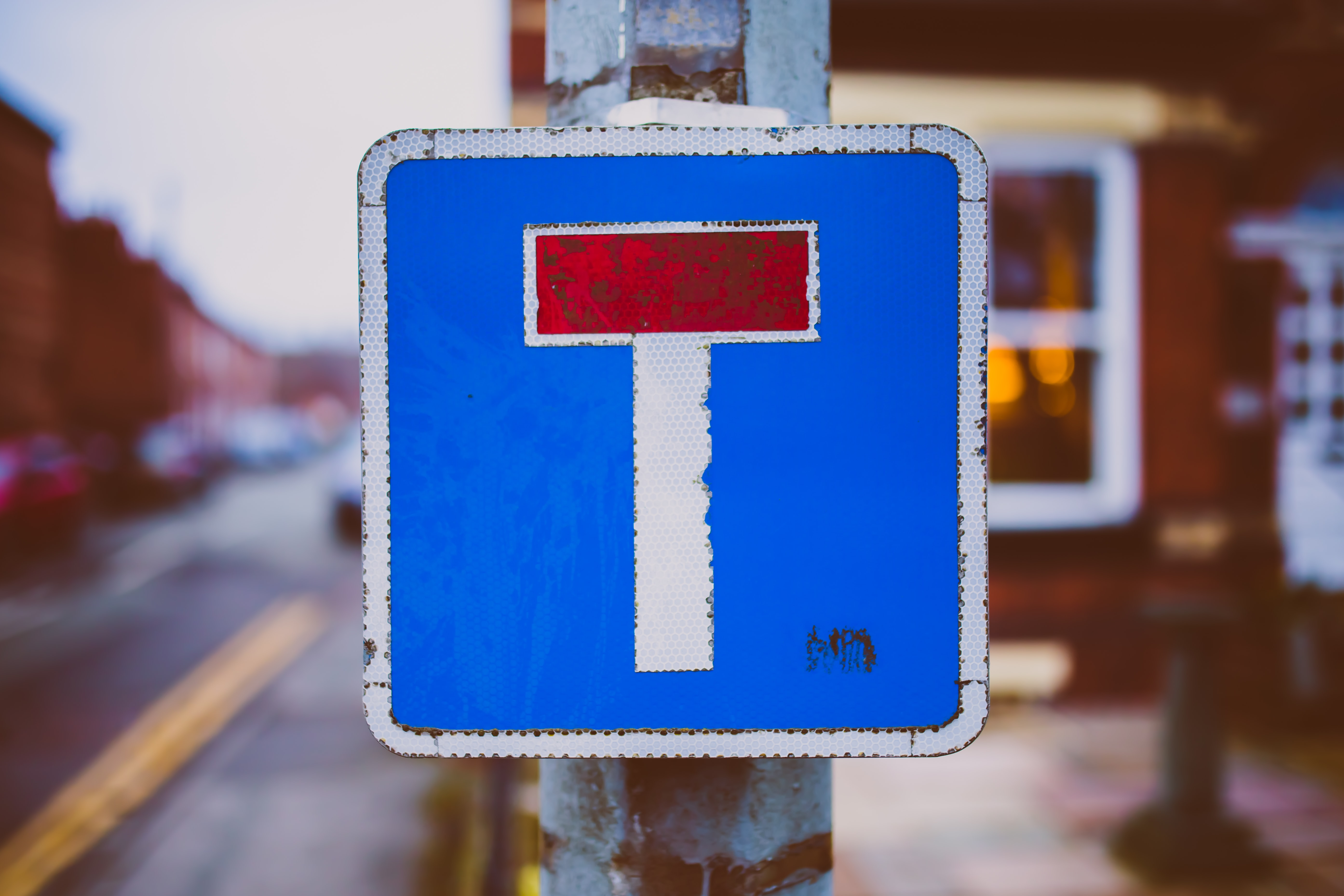 white, blue, and red road sign near road