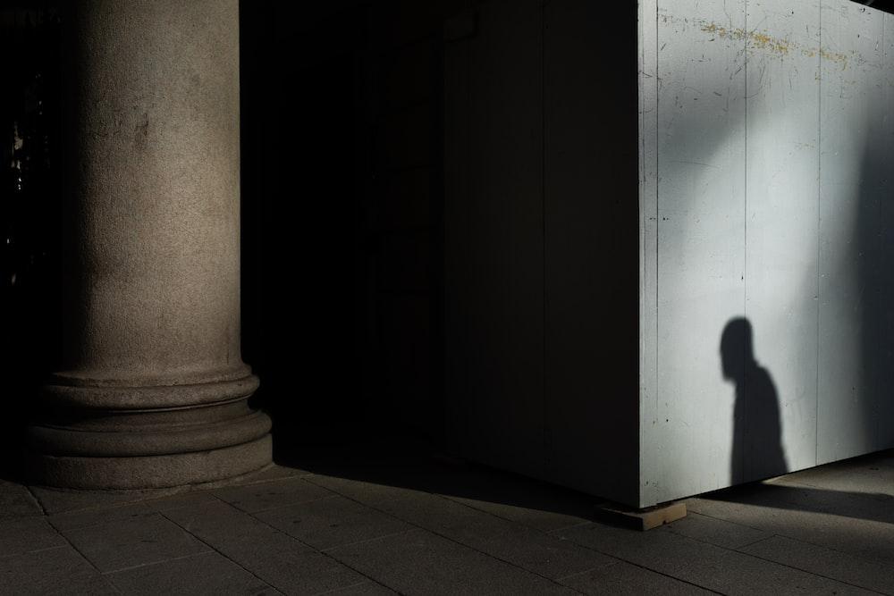 gray concrete pillar near wall