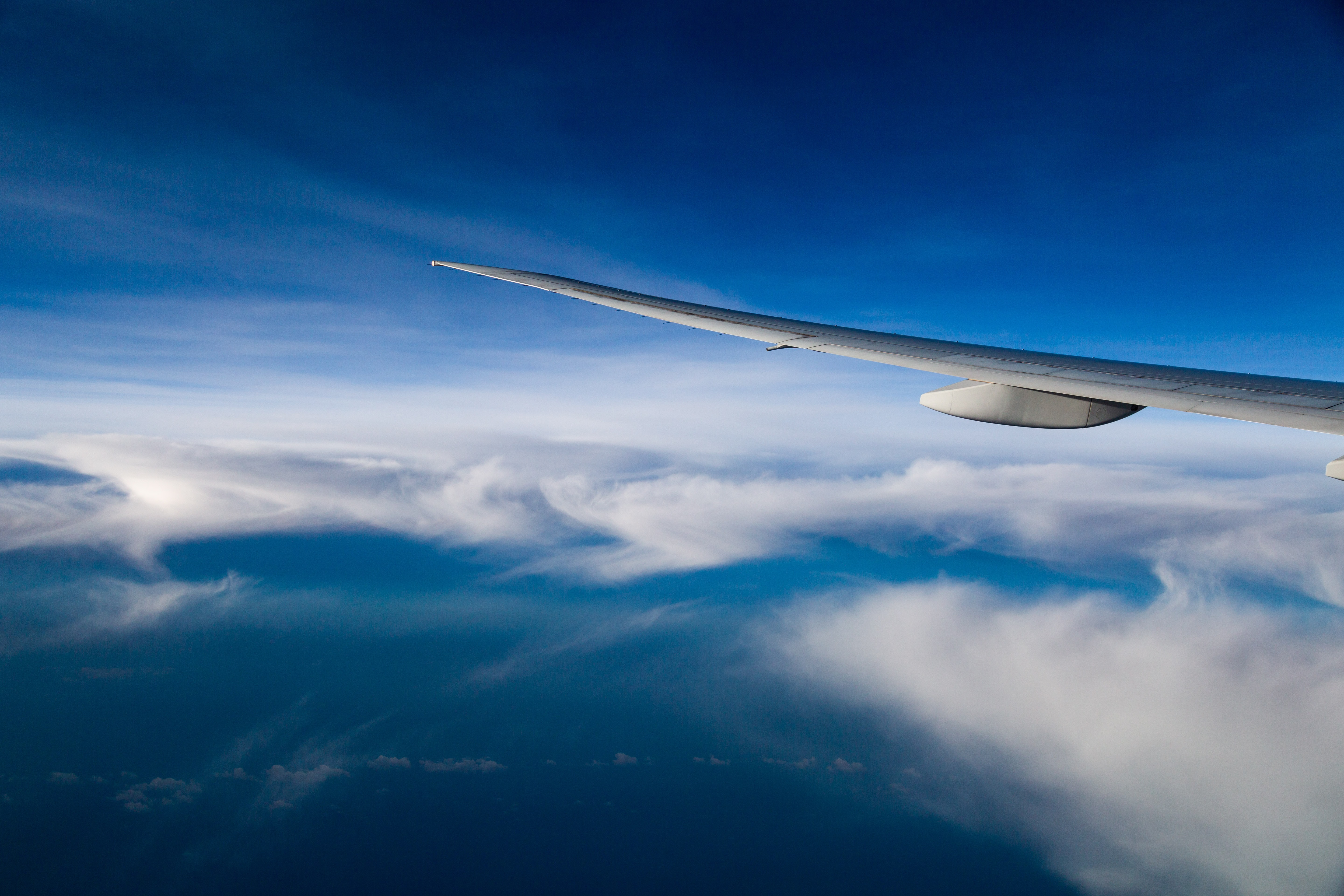 plane over white and blue clouds
