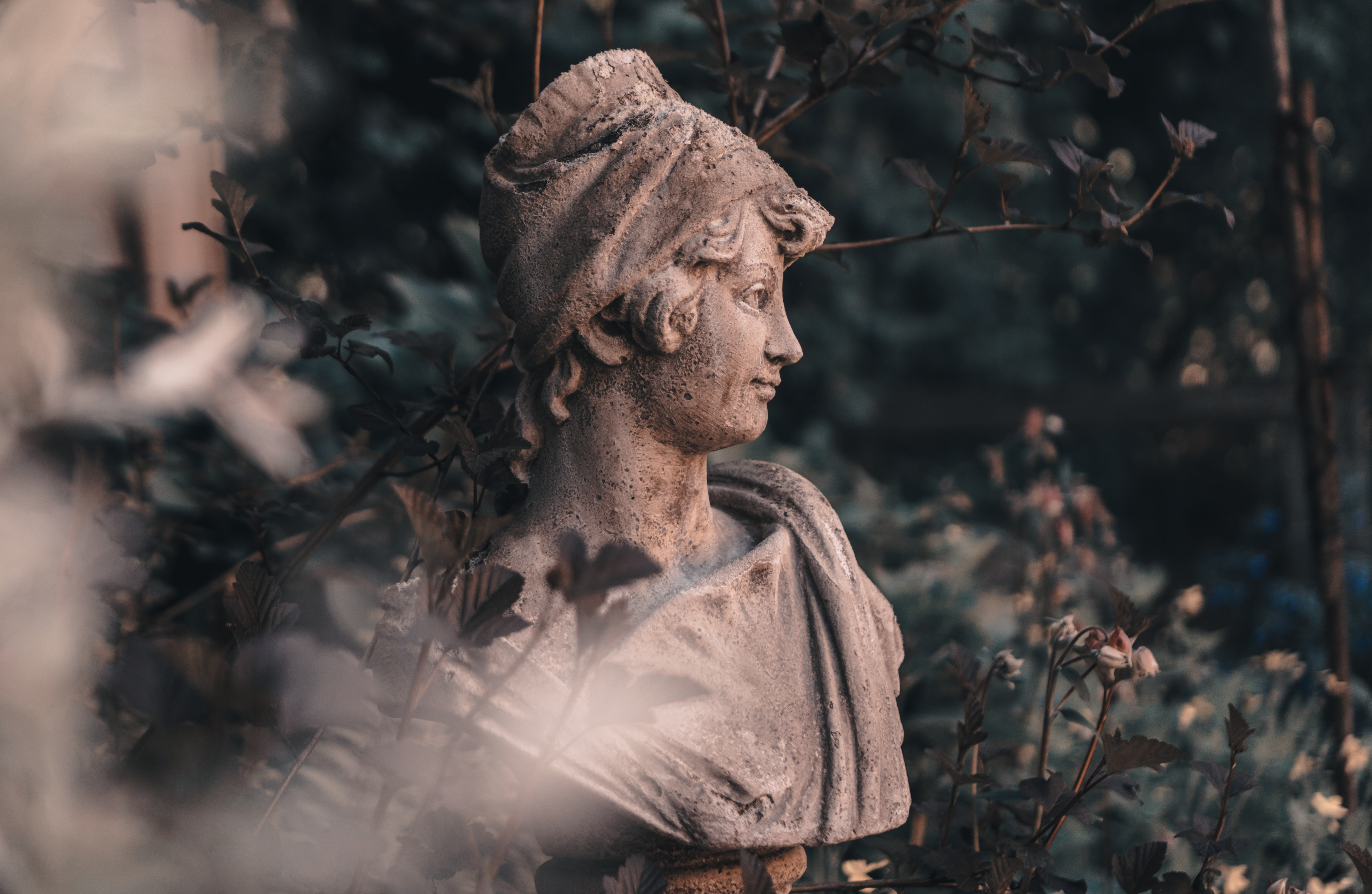 female concrete statue surrounded by green leaves