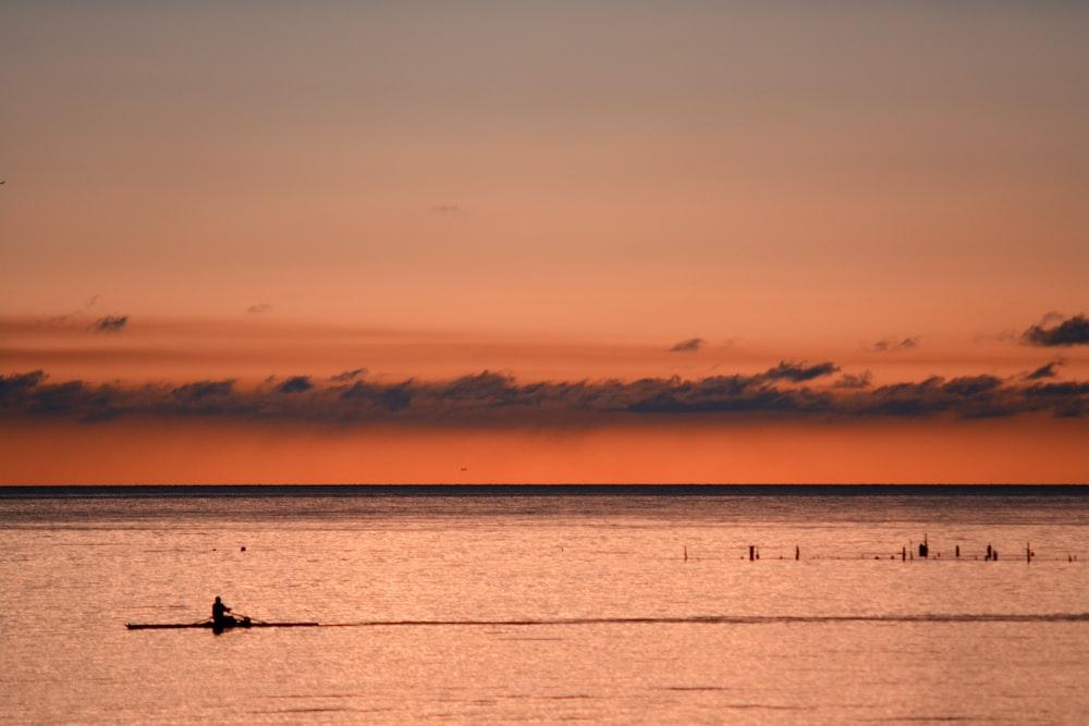 person kayaking during sunset