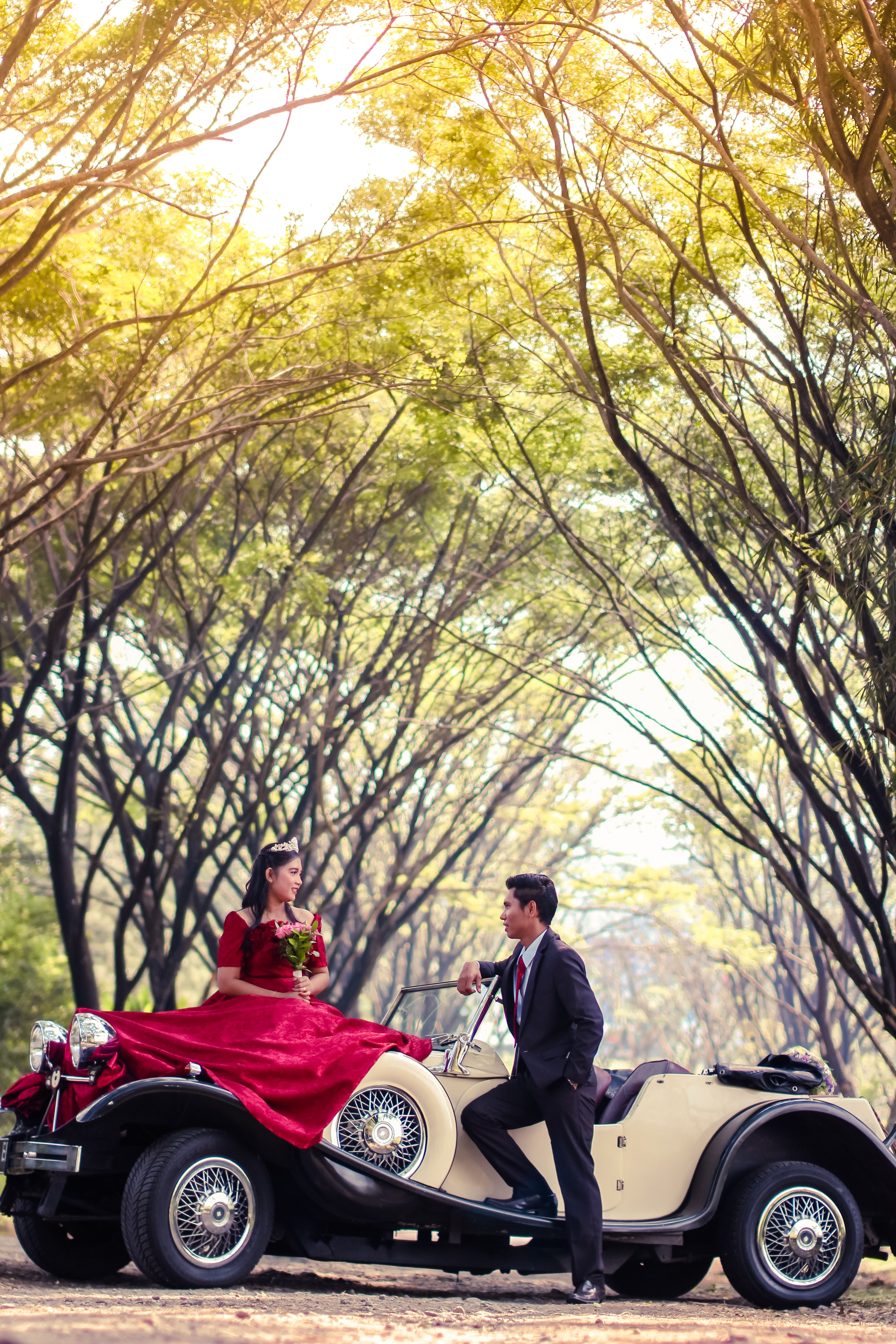 groom and bride on classic car surrounded by trees