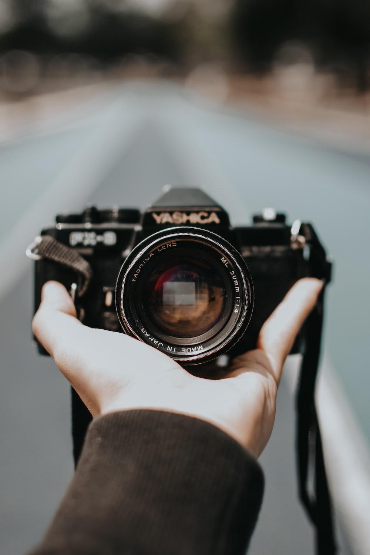 person holding black Yashica camera