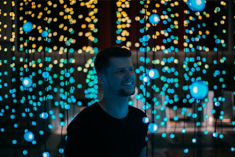 man standing between lighted drop string lights
