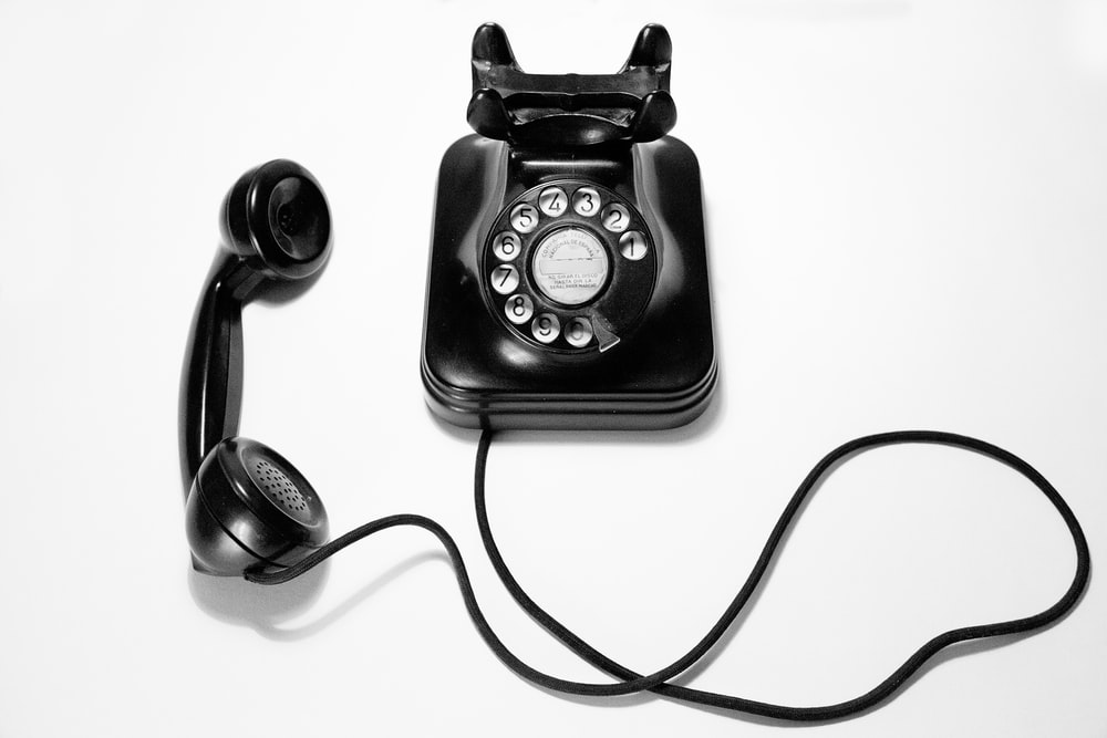 black rotary dial phone on white surface