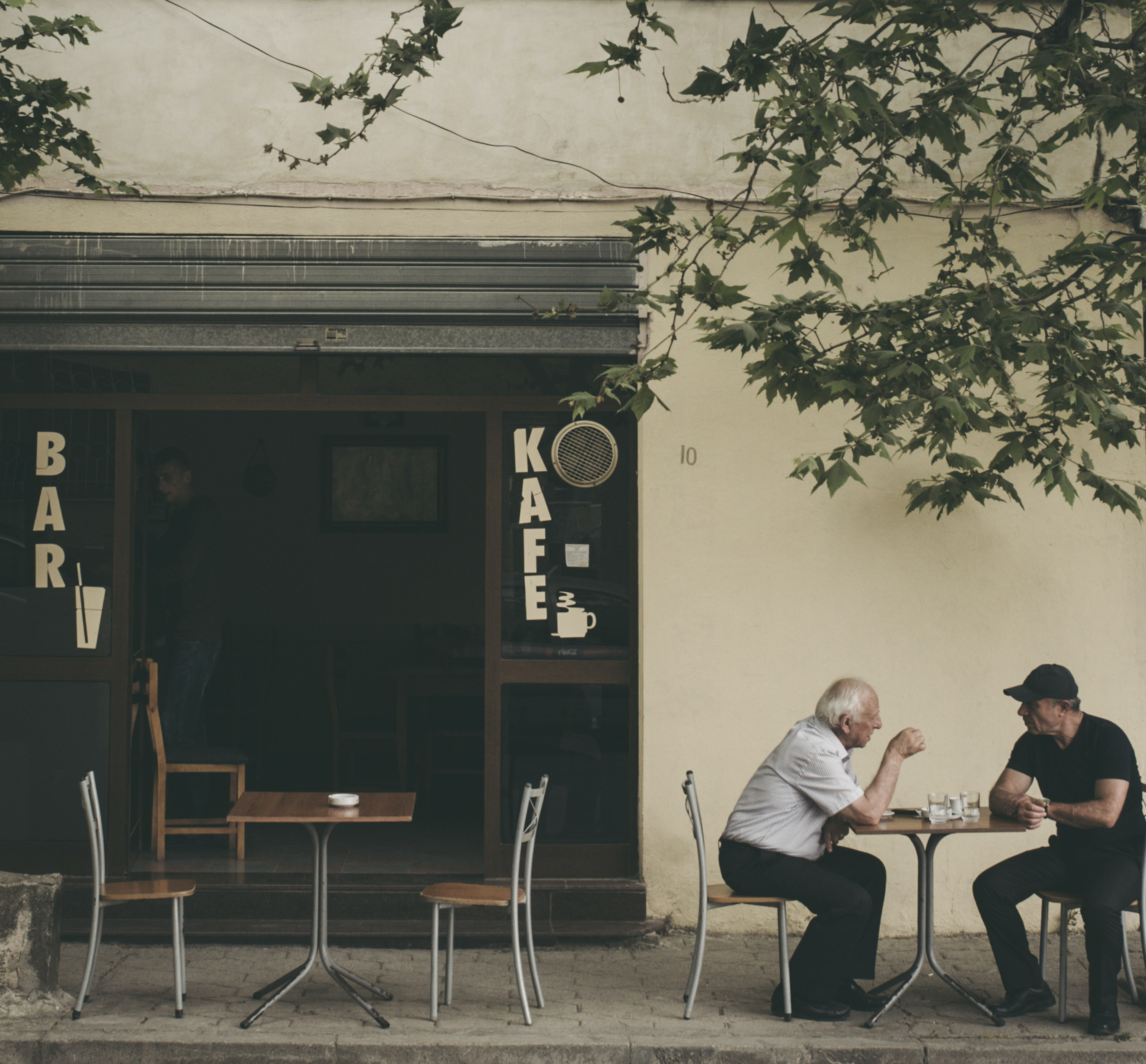 two man chatting white sitting on brown wooden chair