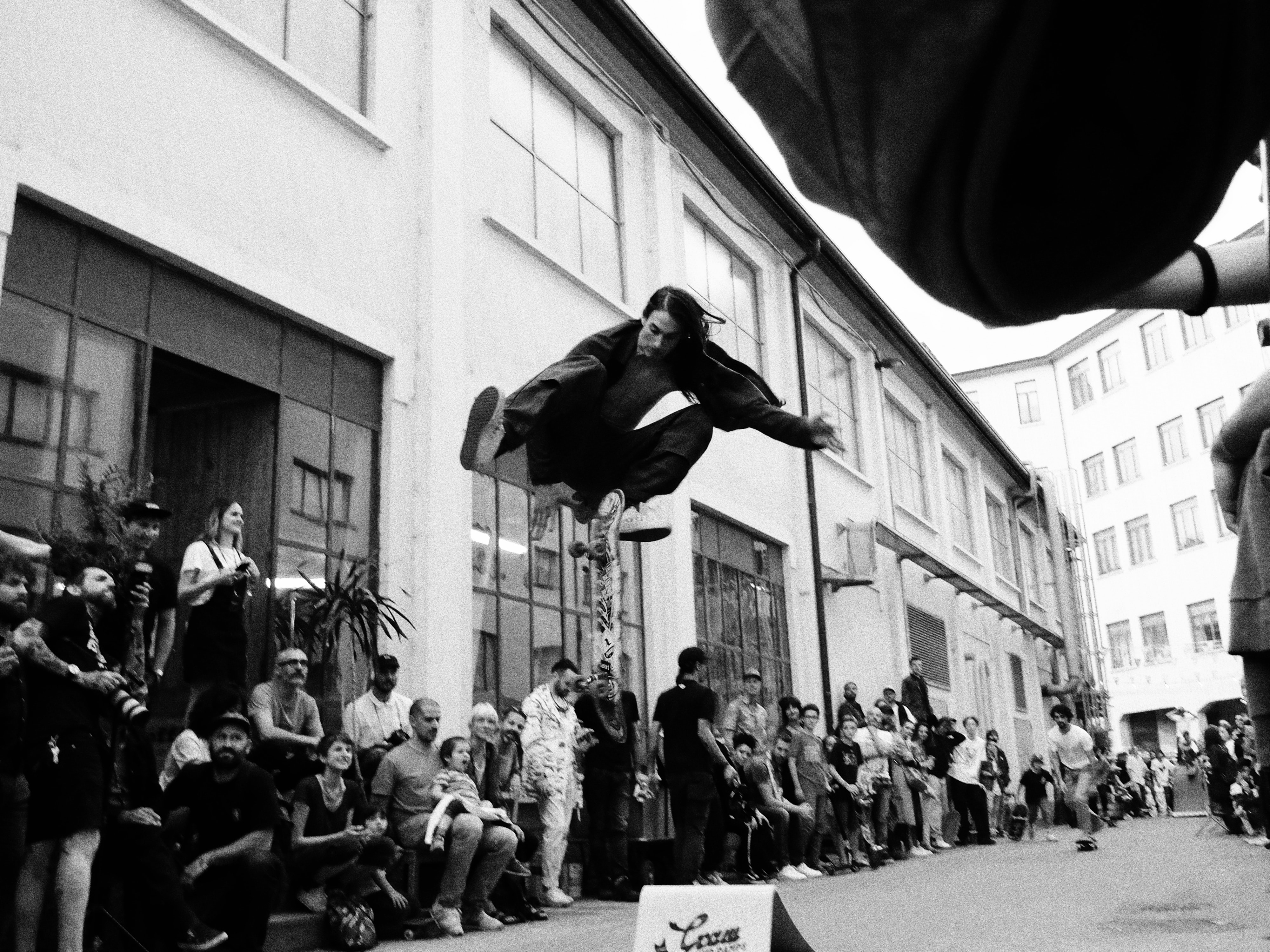 greyscale photo of man jumping on street