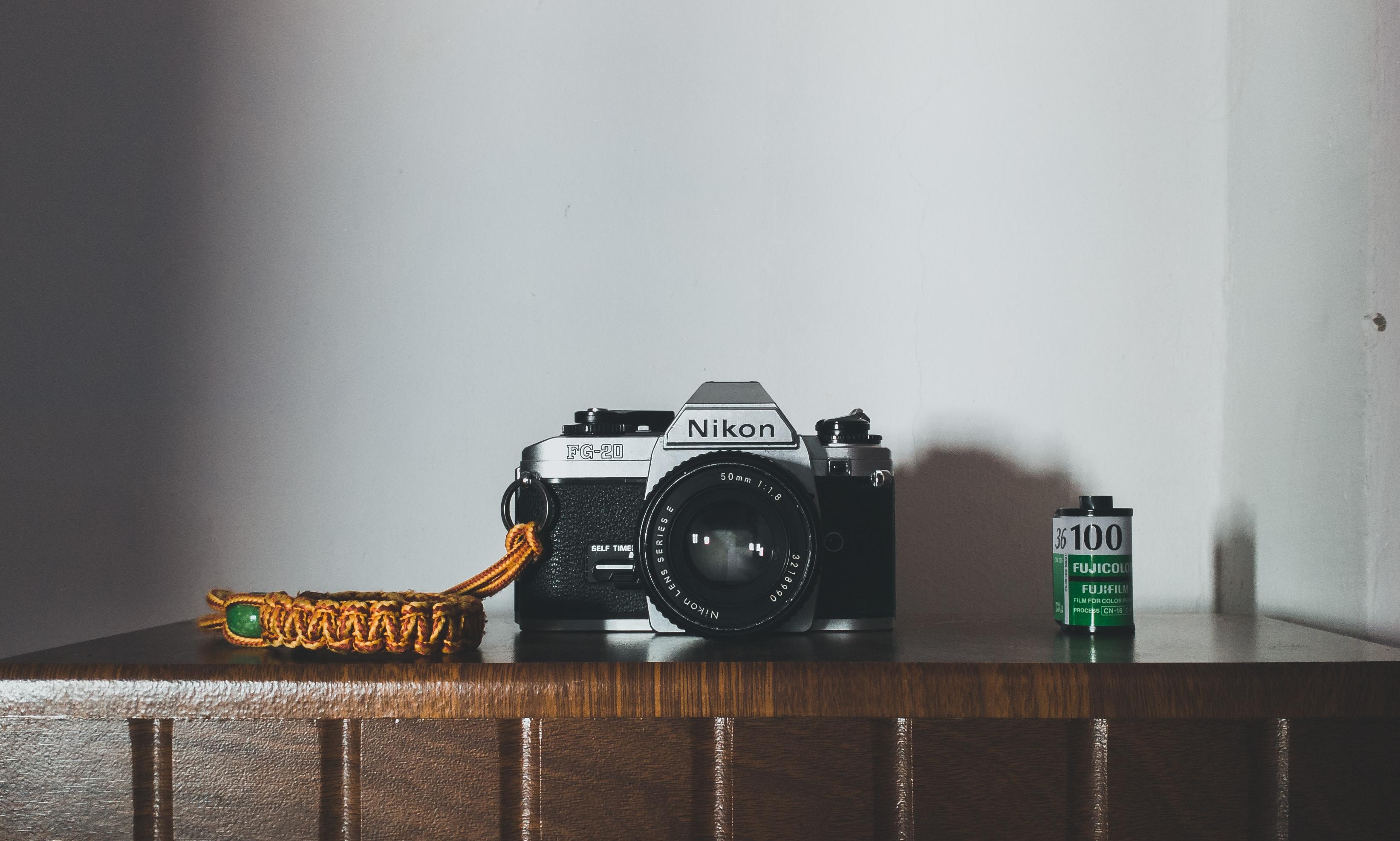black and gray Nikon SLR camera on table