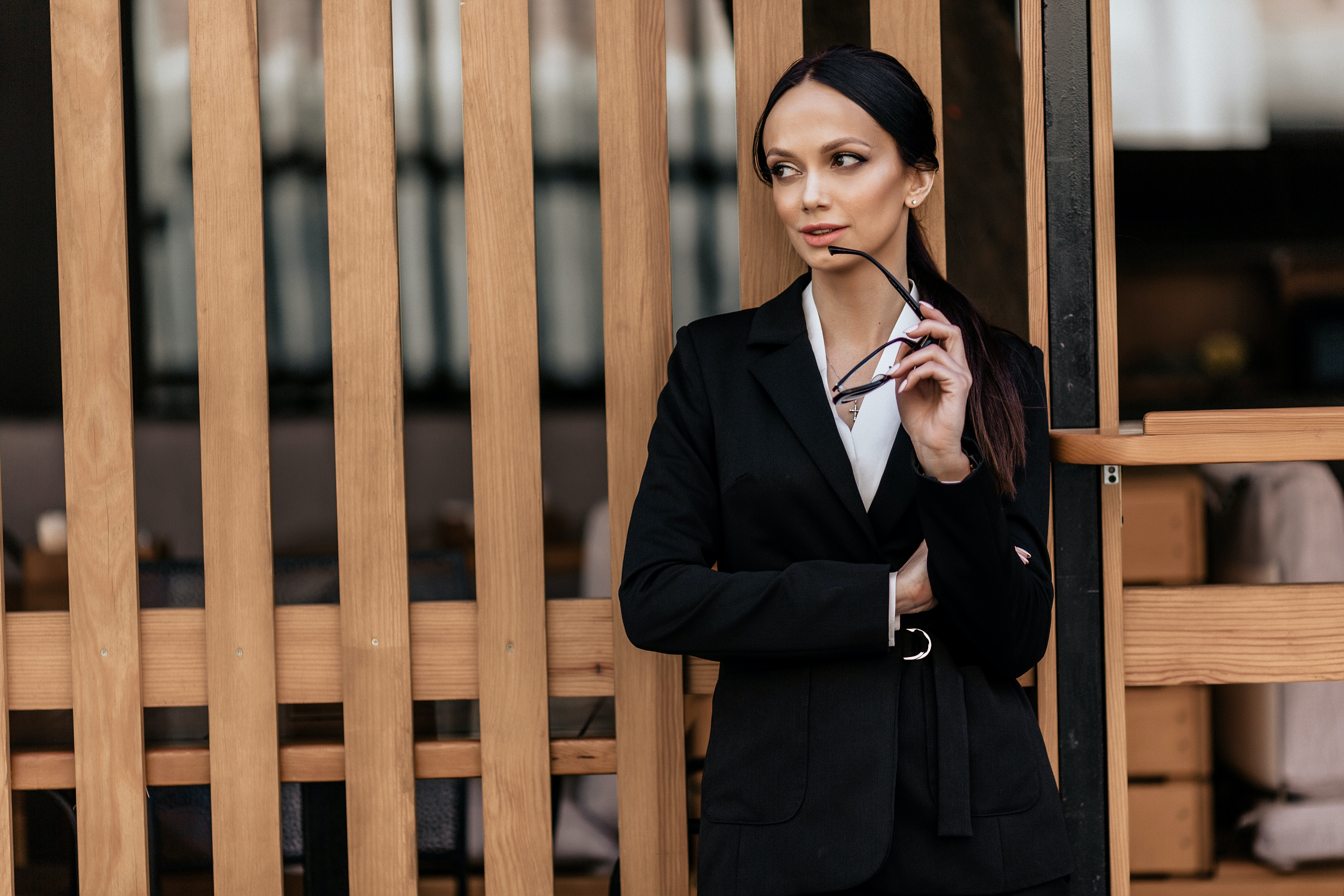 woman leaning against wall wearing black suit jacket