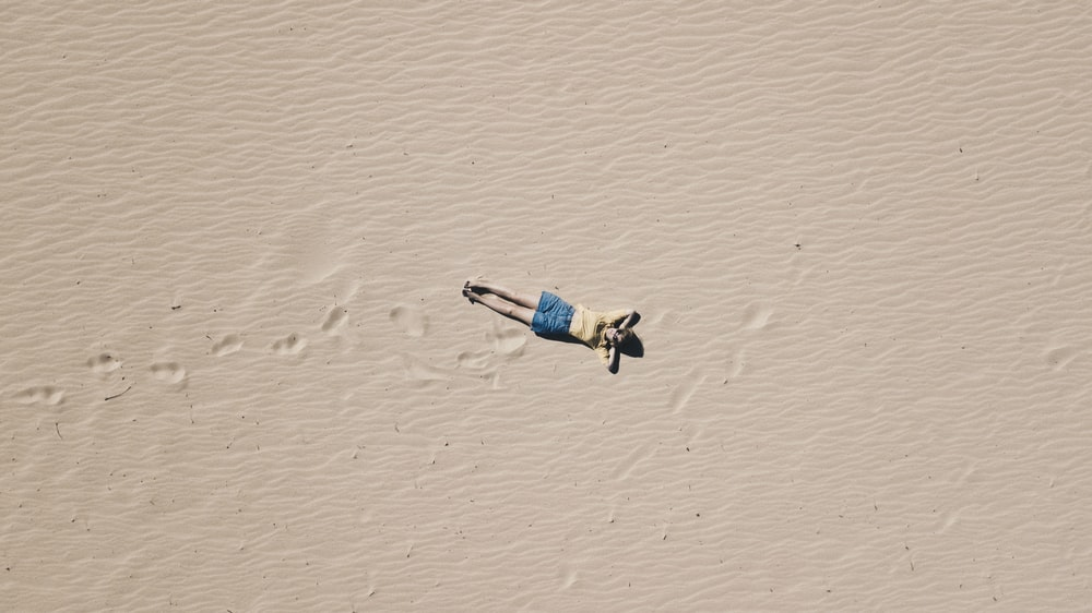 aerial photograph of man lying on sand