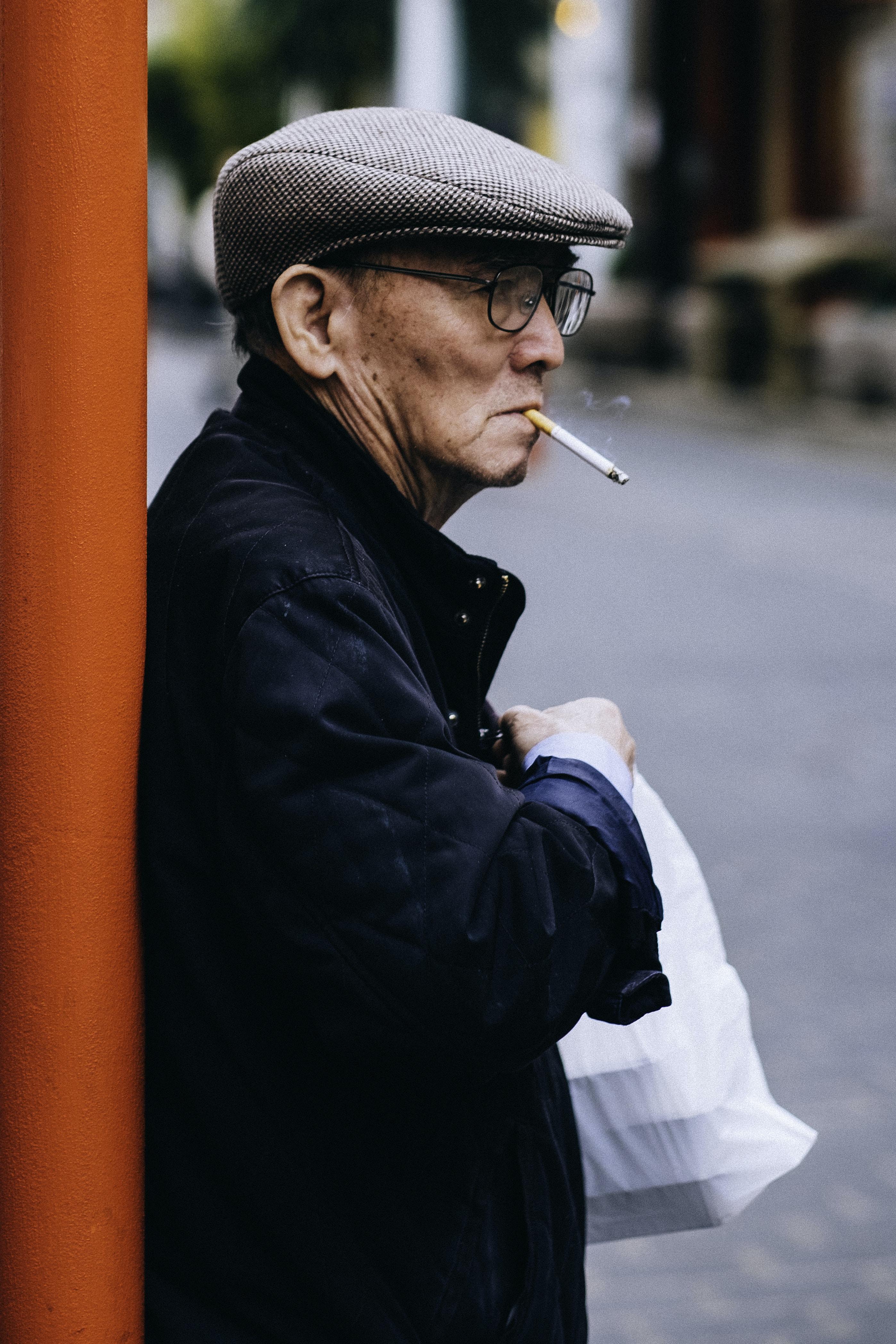 man standing beside post holding plastic bag