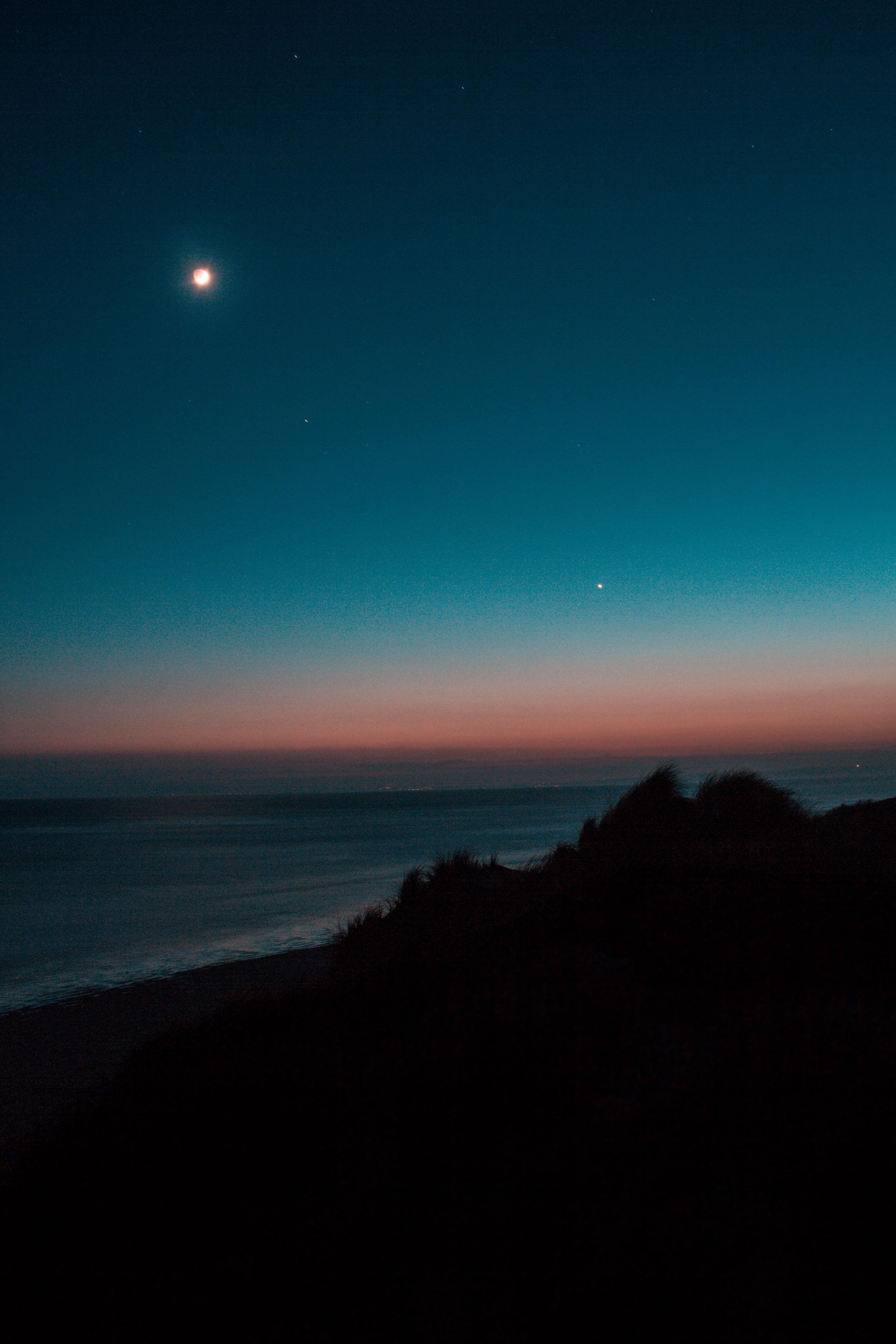 landscape photography of seashore against blue and orange skies