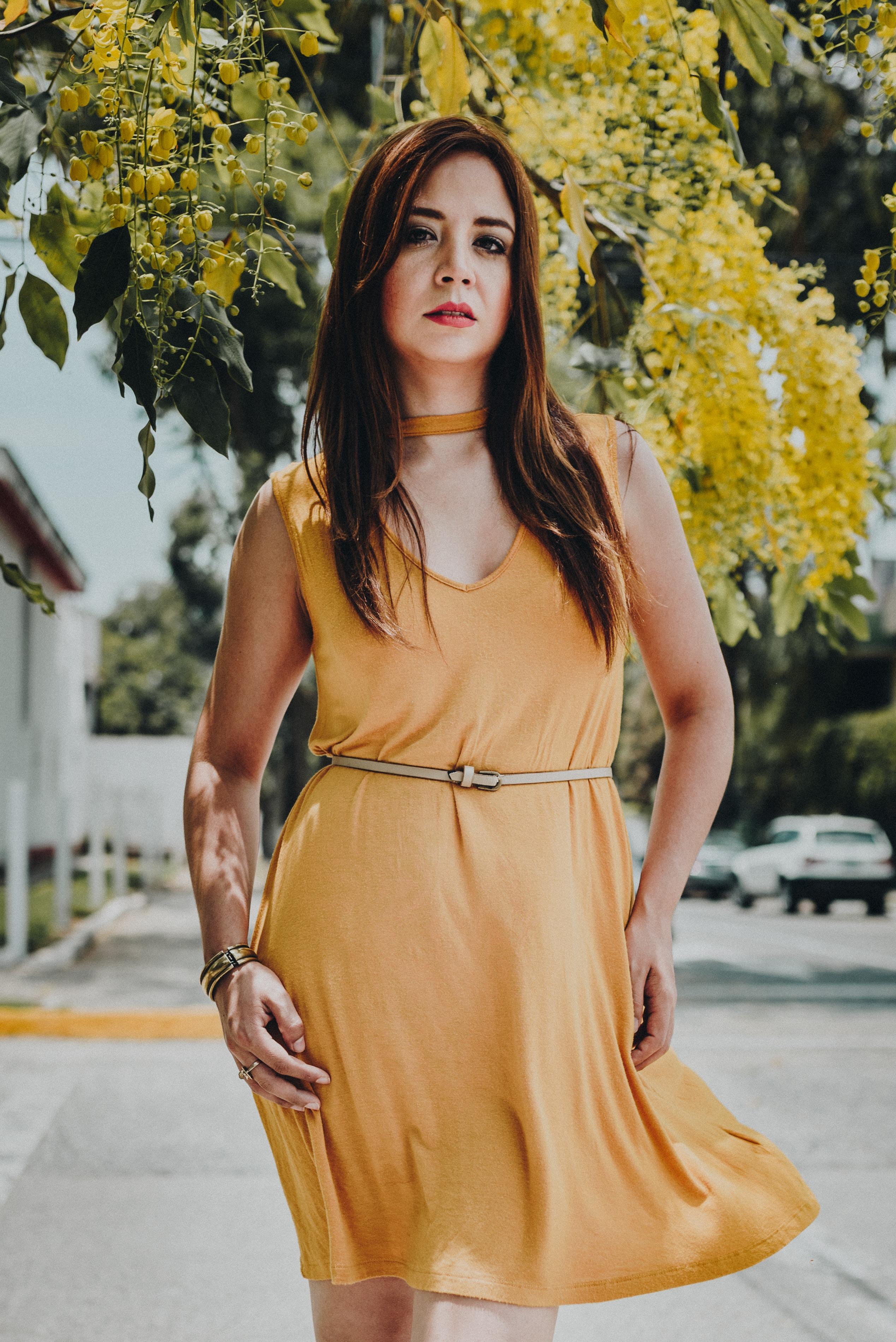 woman wearing orange sleeveless dress standing near yellow flower tree