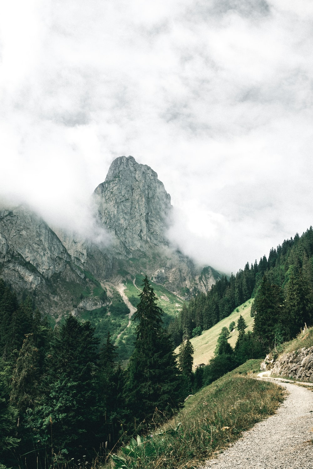 photograph of mountain surrounded by clouds