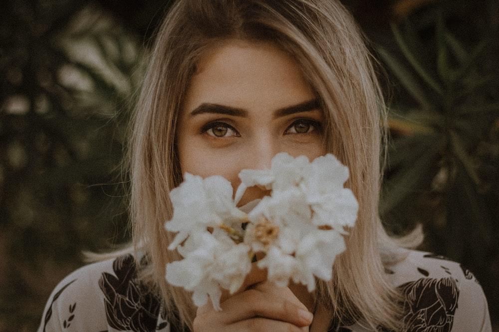 woman holding white petaled flower