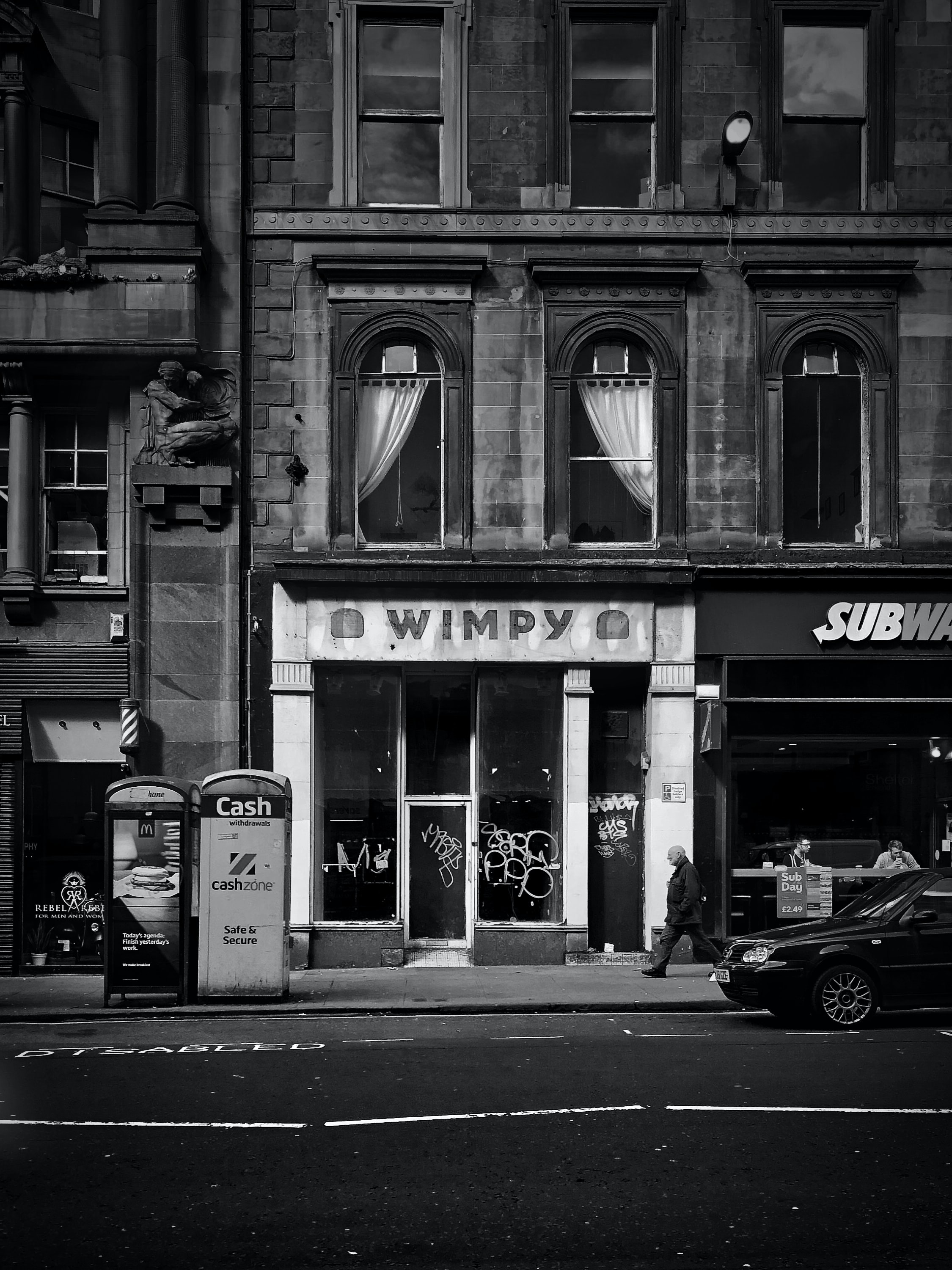 grayscale photo of person waking on street beside Wimpy boutique
