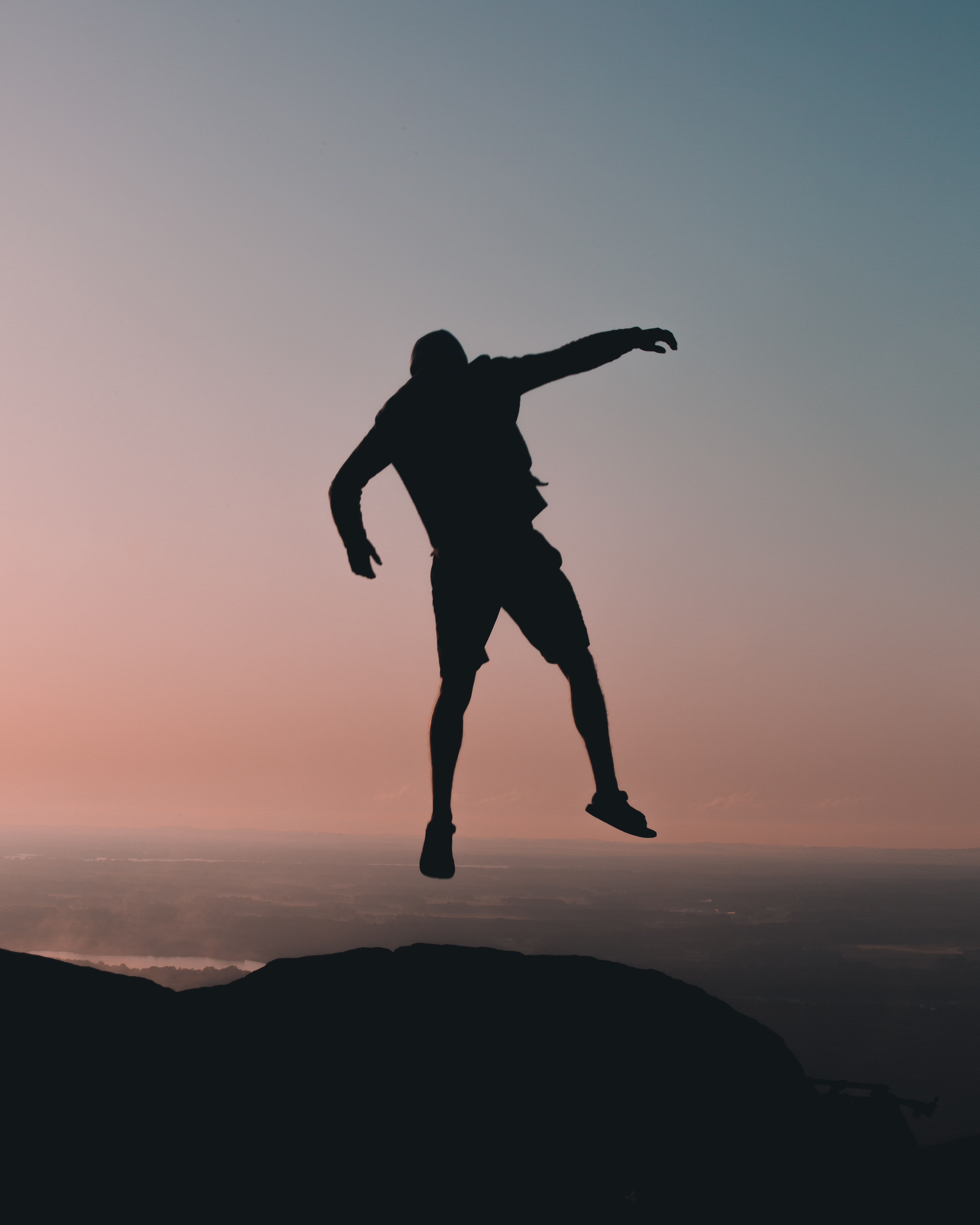 silhouette of man jumping on cliff at golden hour