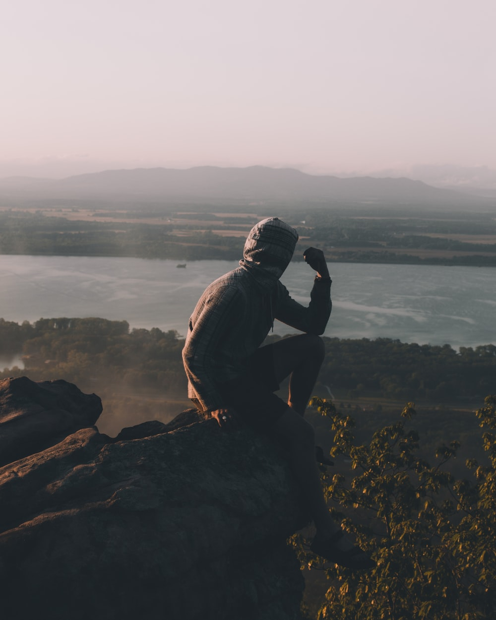 man sitting on cliff over body of water