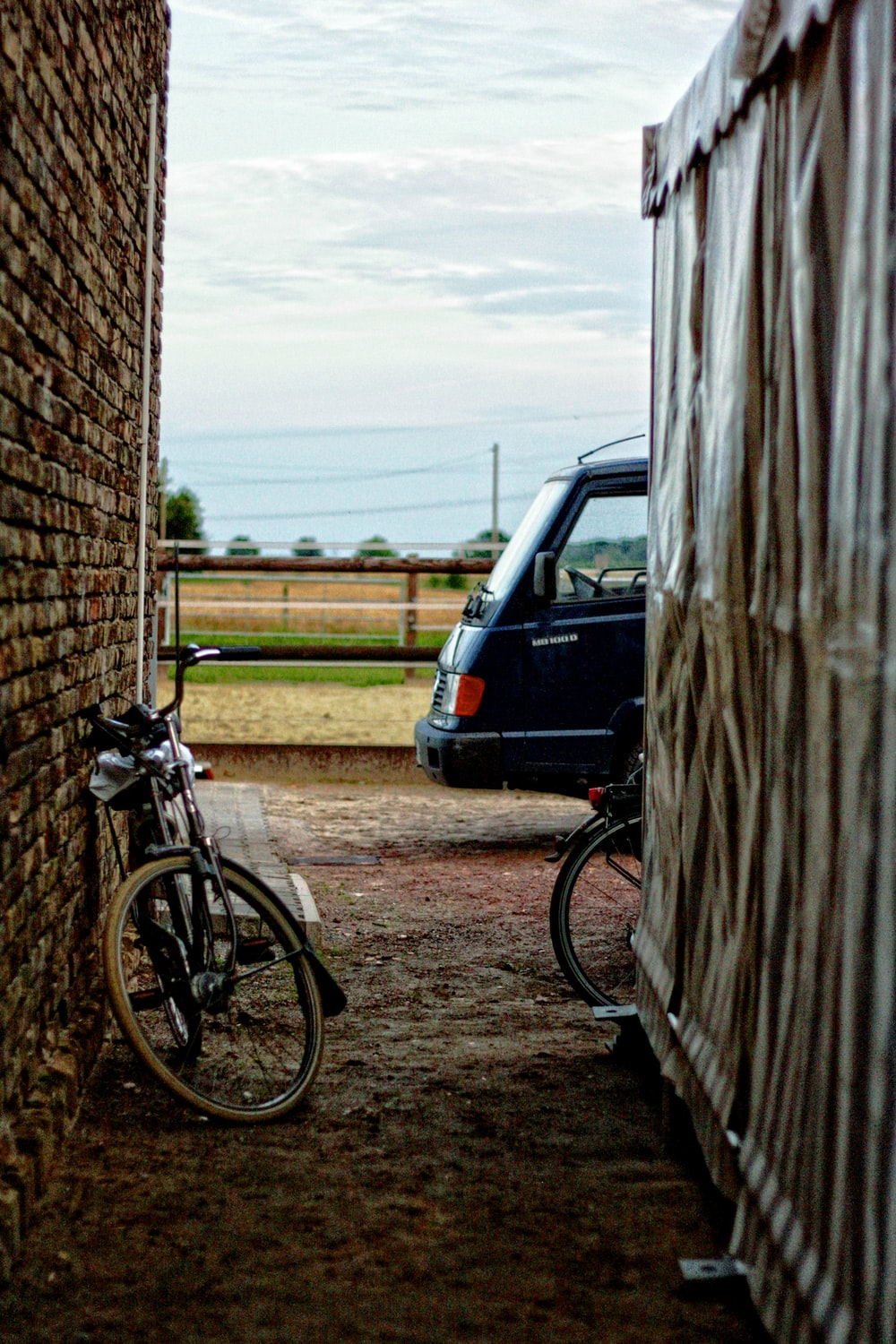 black bicycle leaning on brown wall