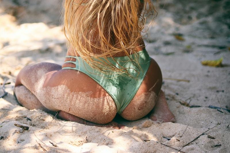 woman wearing green bikini bottom sitting on sand