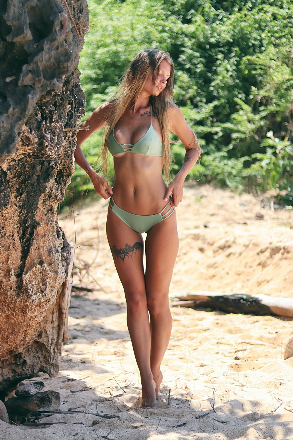 woman wearing green bikini near brown rock