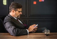 man using smartphone beside wooden table with glass cup on top
