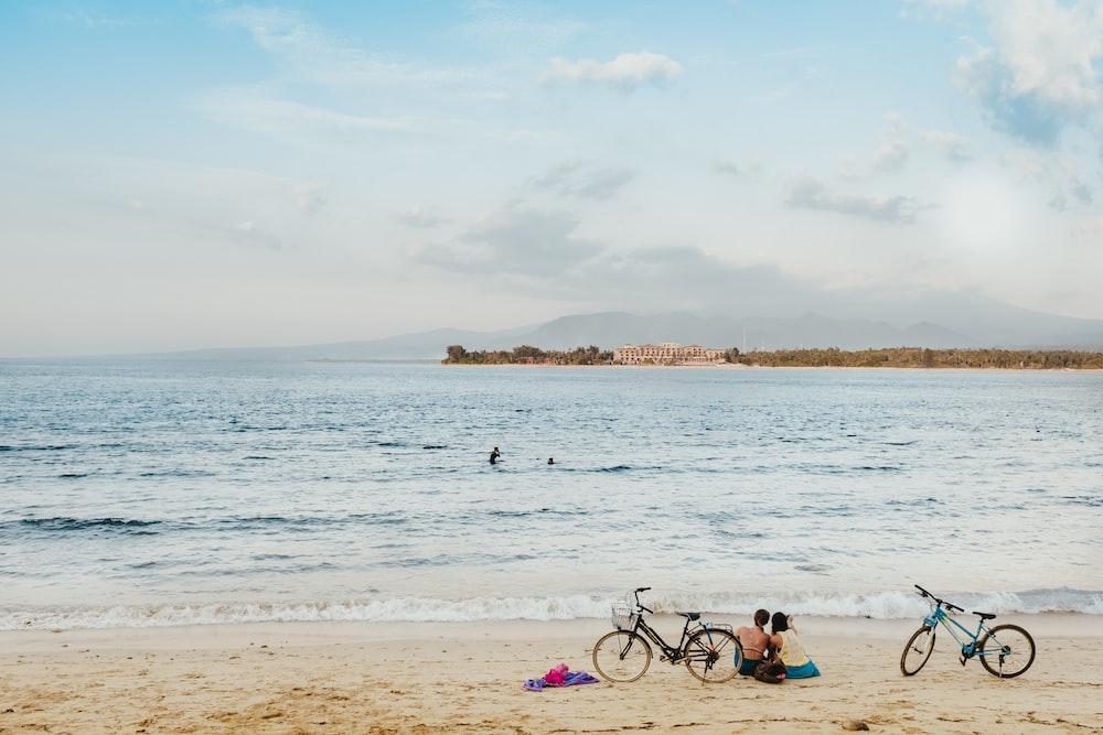 two people sitting on seashore during daytime