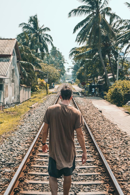 man walking in front of railway