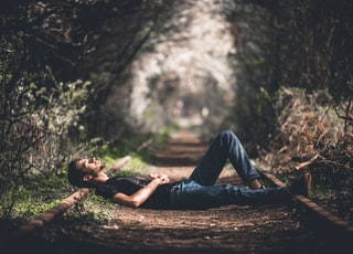 focus photography of man lying on pathway with plants