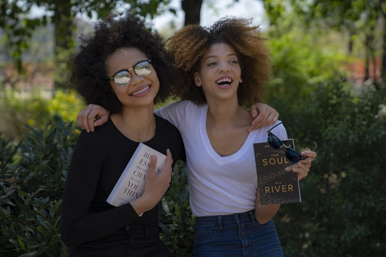 Two young, black women with natural hair smiling with their arms around each other, holding books. To demonstrate a study showing that feeling love in everyday life makes us happier!
