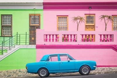 blue coupe in front of pink house cape town teams background