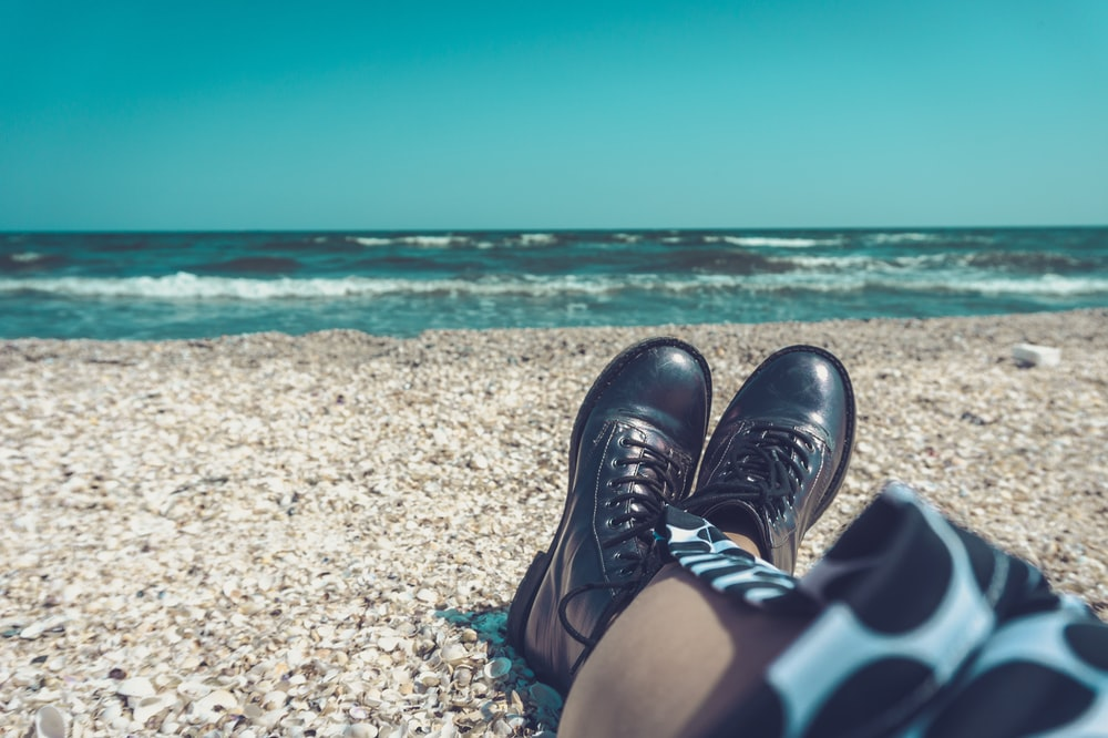 person wearing pair of black leather shoes sitting on seashore