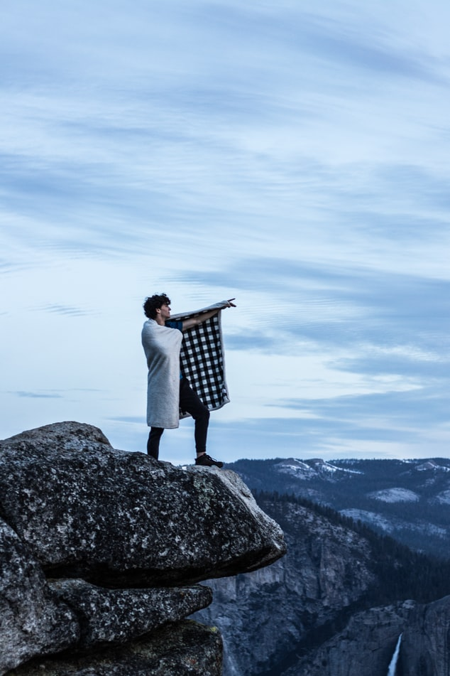 man on cliff with blanket
