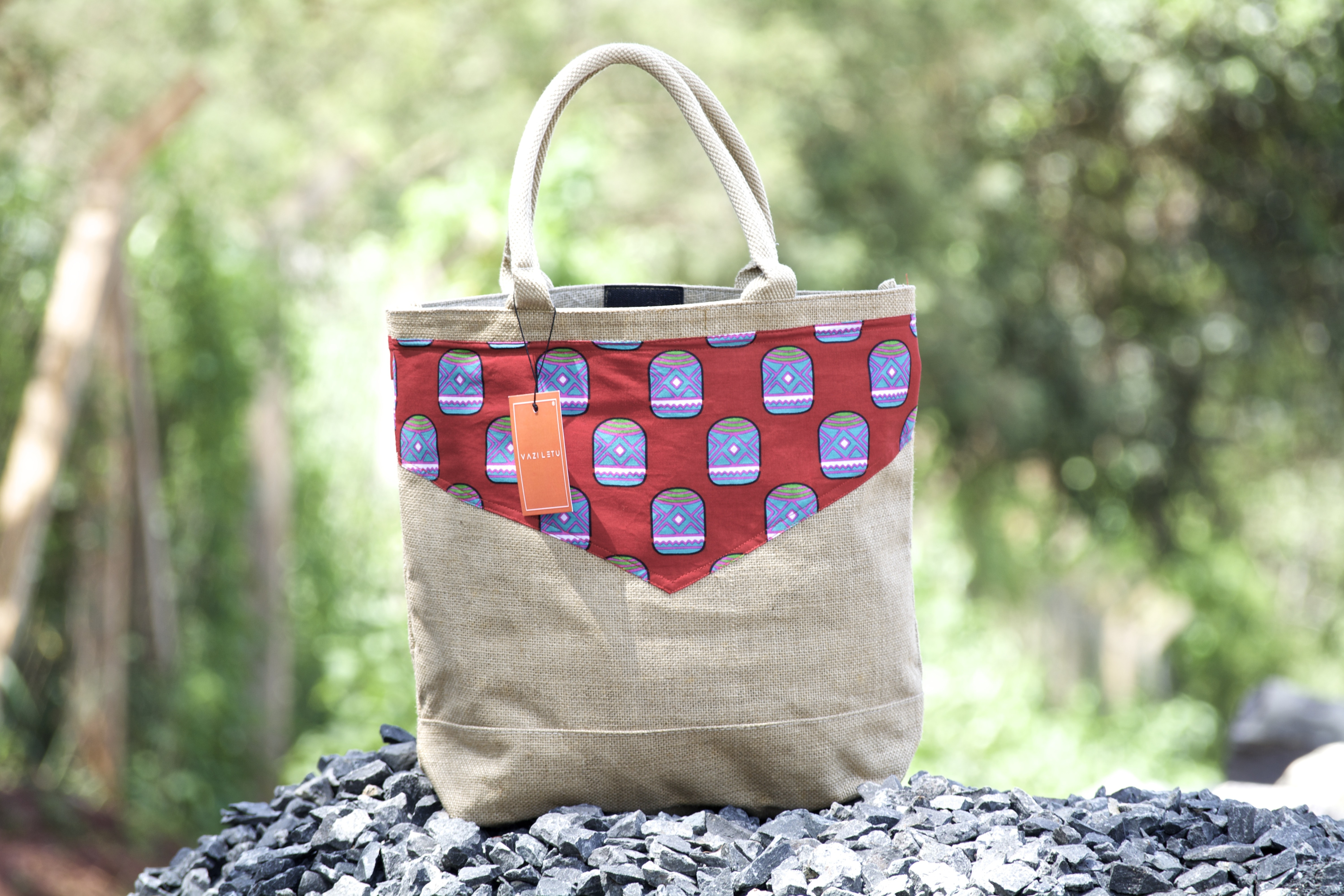 women's brown and red leather tote bag on top of gravel