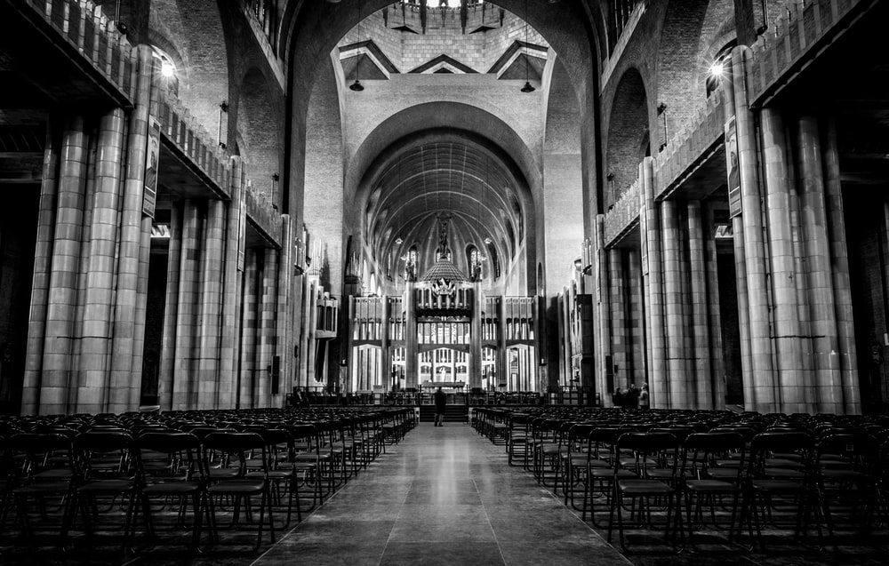 grayscale photo of man standing in front of altar