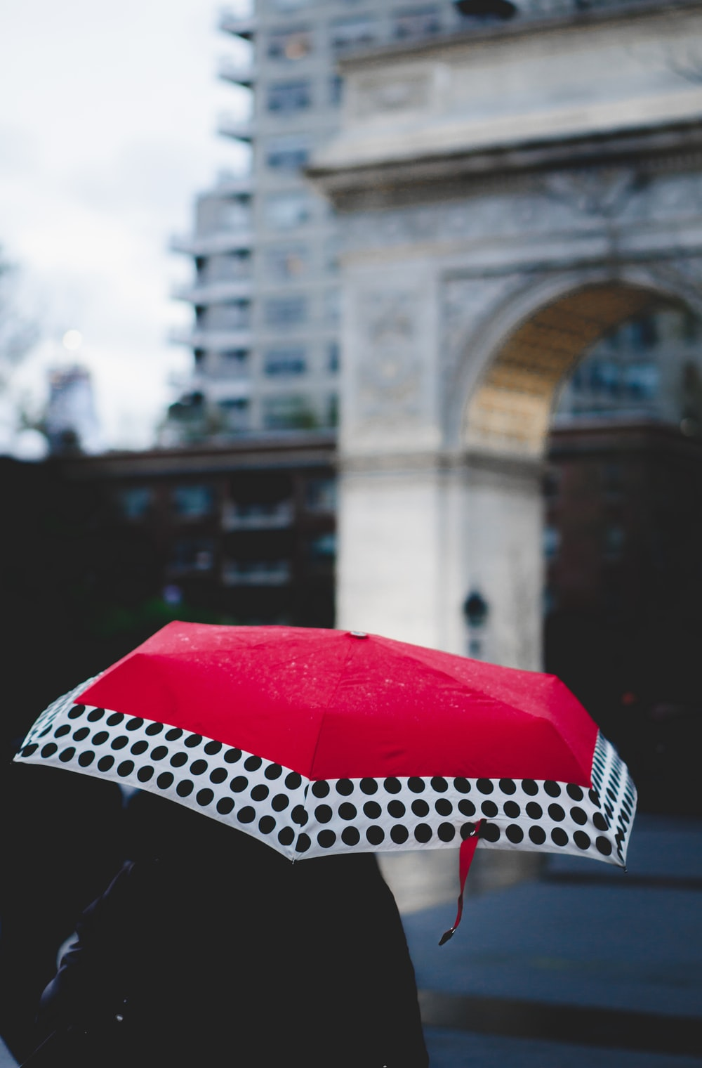 person under red and white umbrella walking near building
