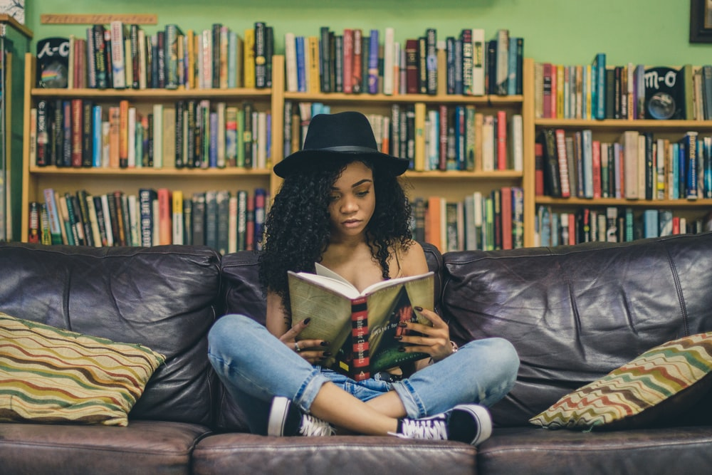 woman reading a book while sitting on black leather 3-seat couch