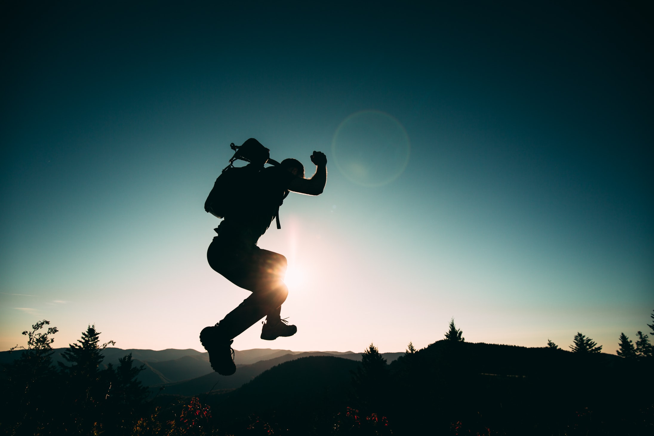 silhouette of jumping person on hill