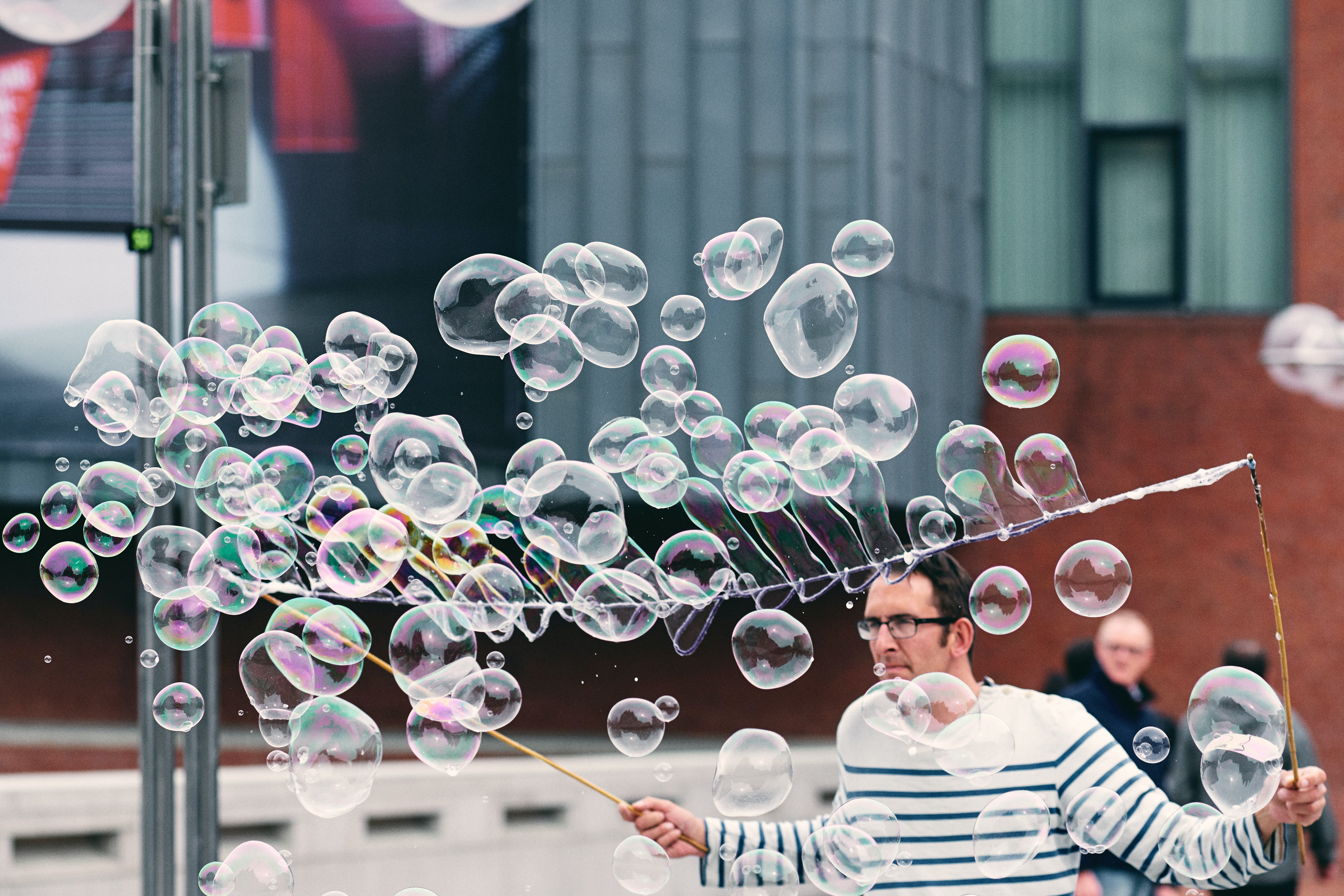 man making soap bubbles during daytime