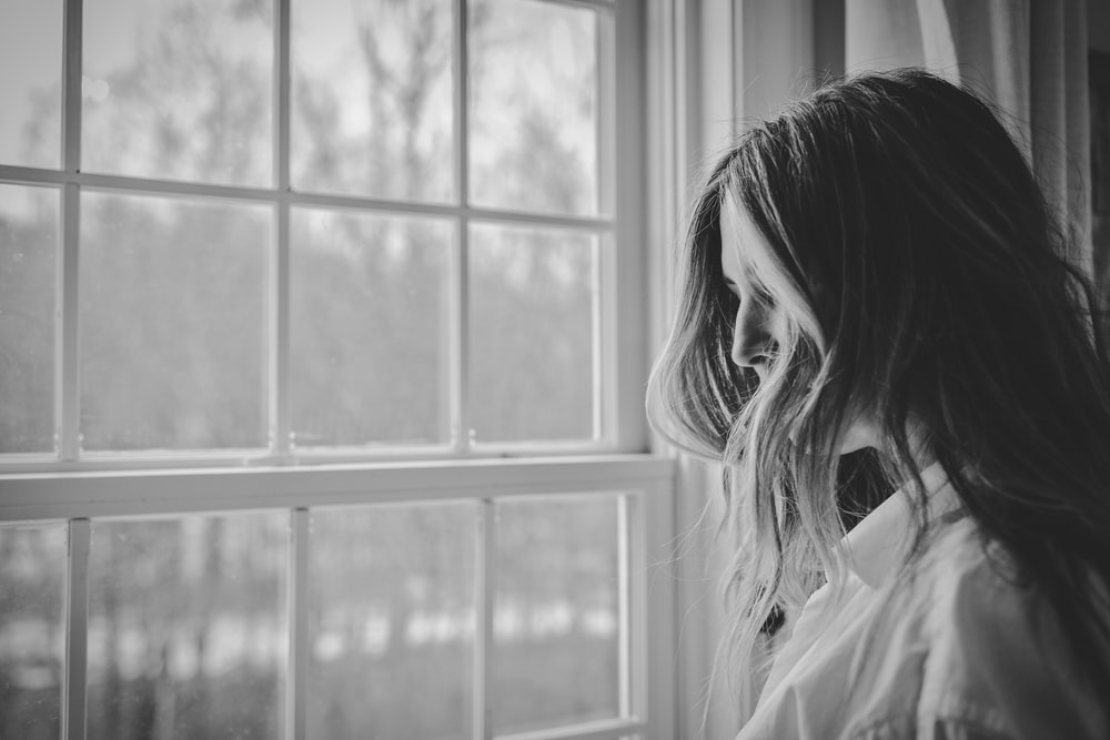 grayscale photo of woman near window