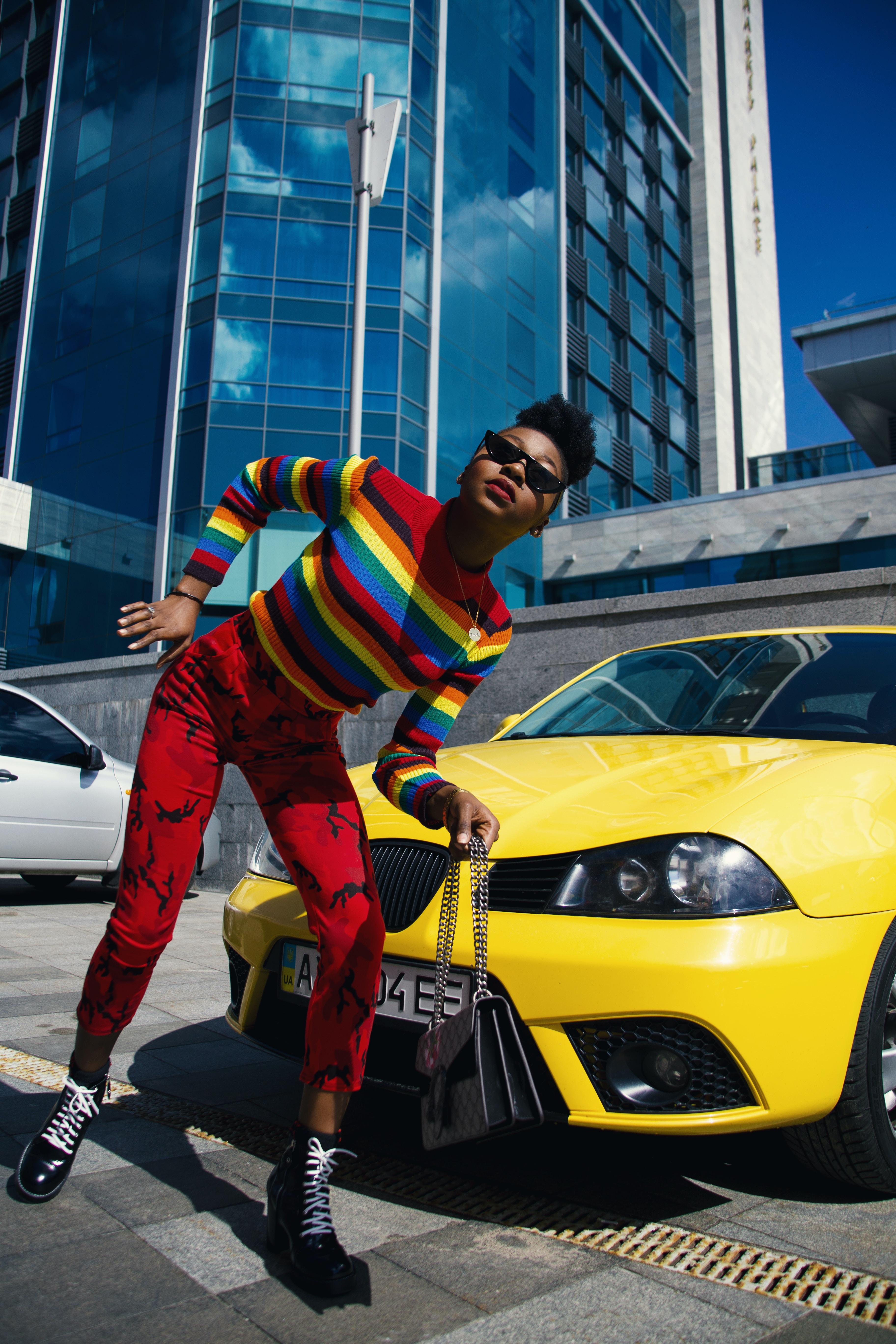 woman beside yellow car during daytime