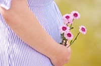 pregnant woman holding petaled flowers