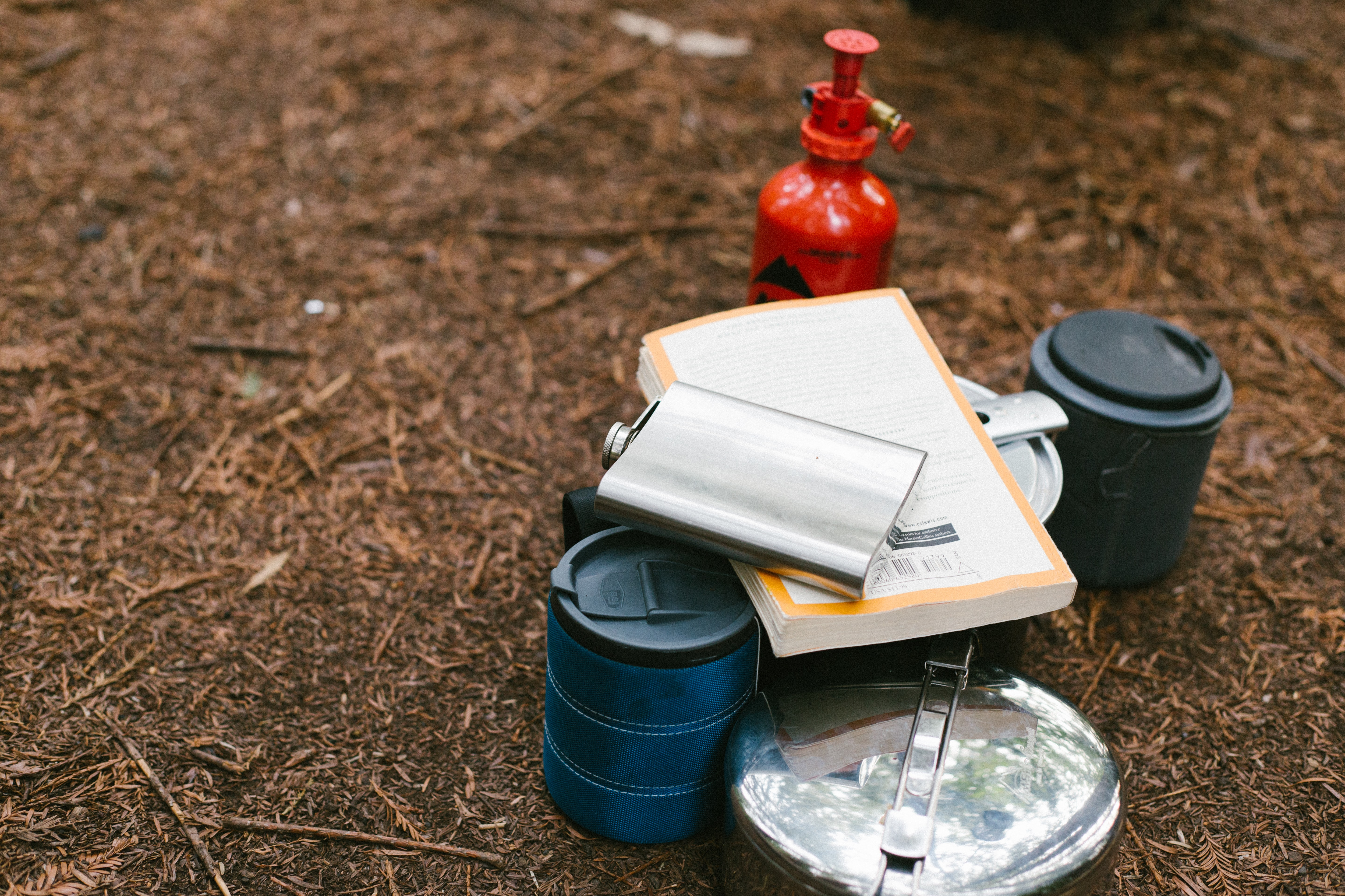 flat lay photography of hip flask, book, tiffin carrier and container