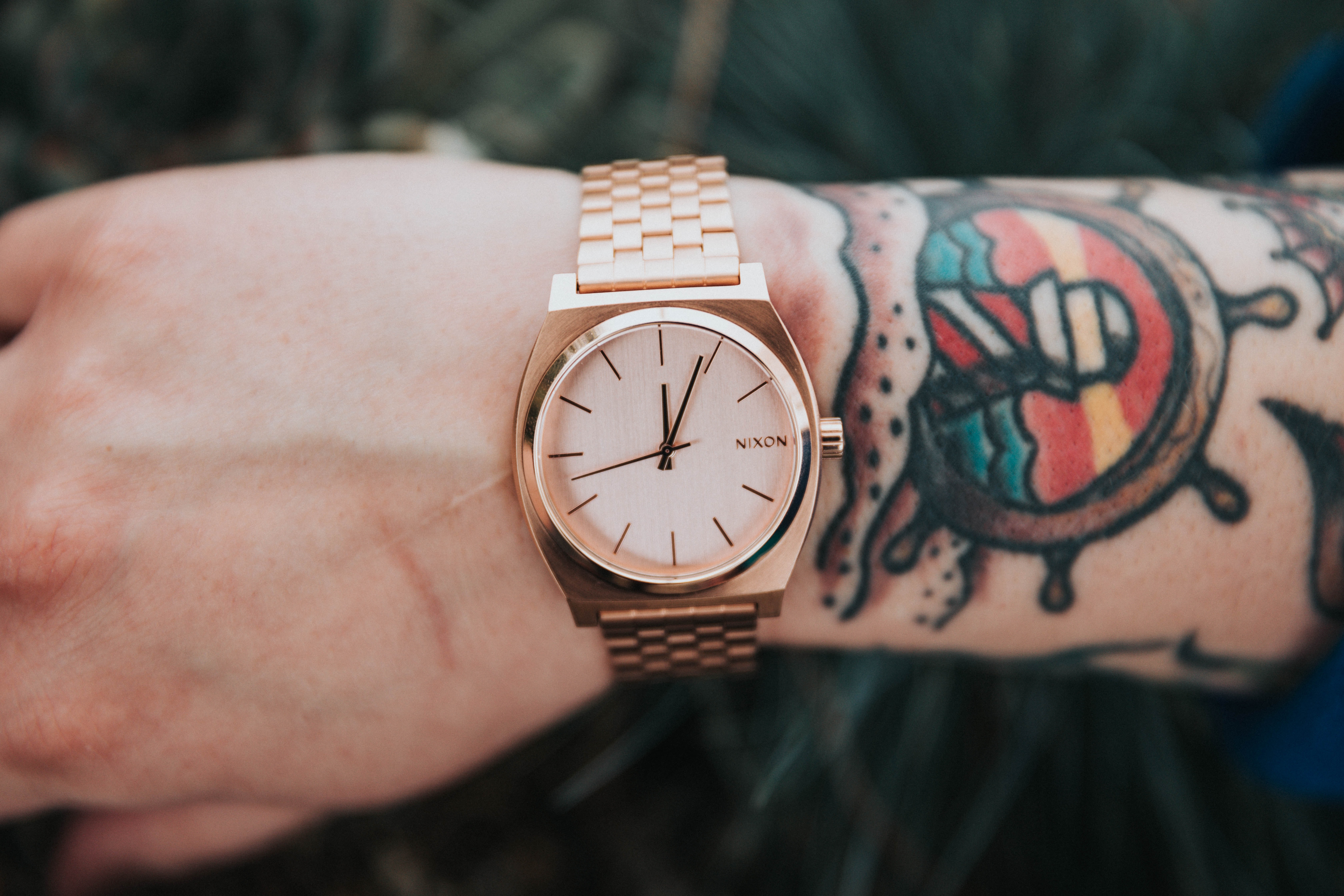 person wearing round gold-colored analog watch display at 12:04 o'clock