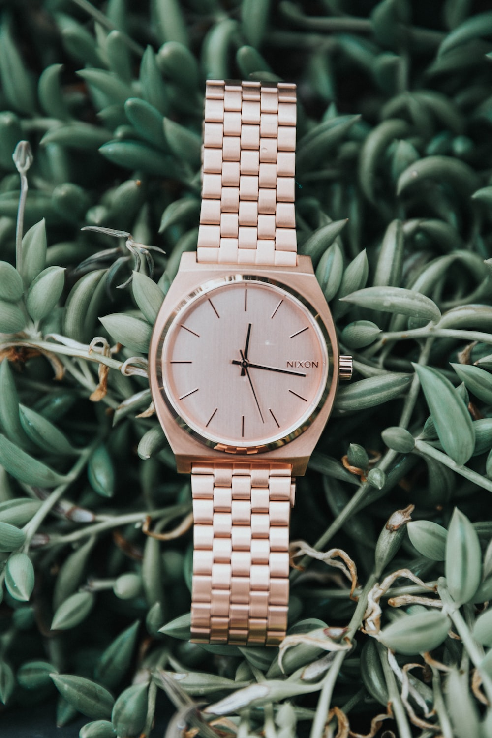 round gold-colored Nixon analog watch with link bracelet